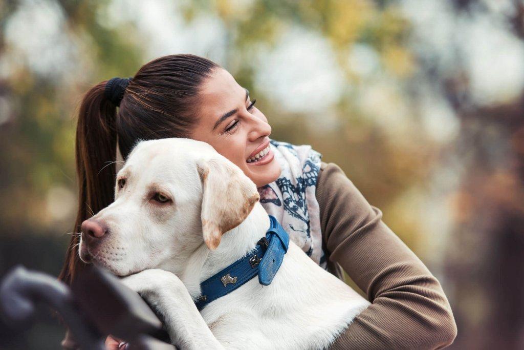 woman hugging white lab dog