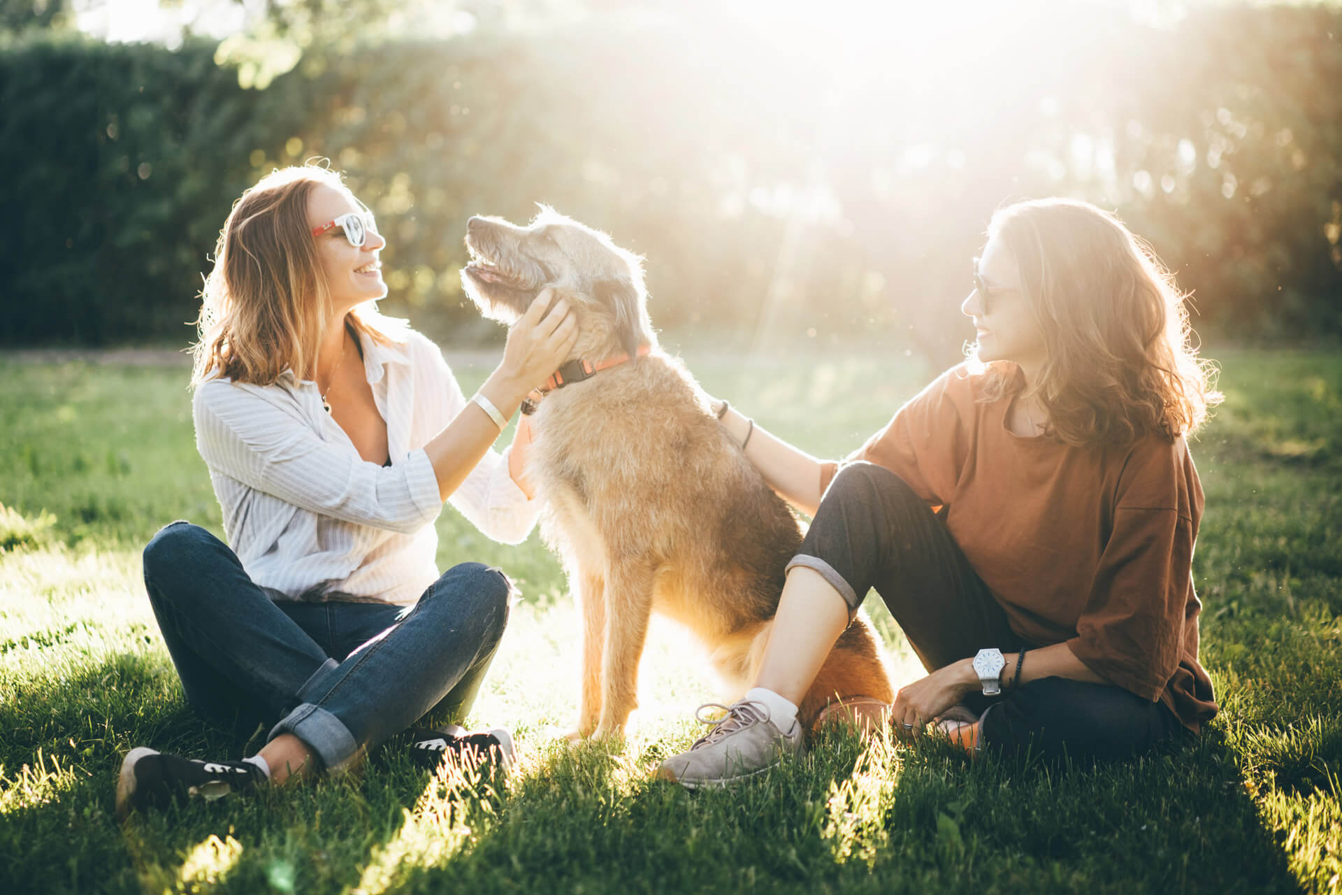two woman sitting down outdoors with a dog