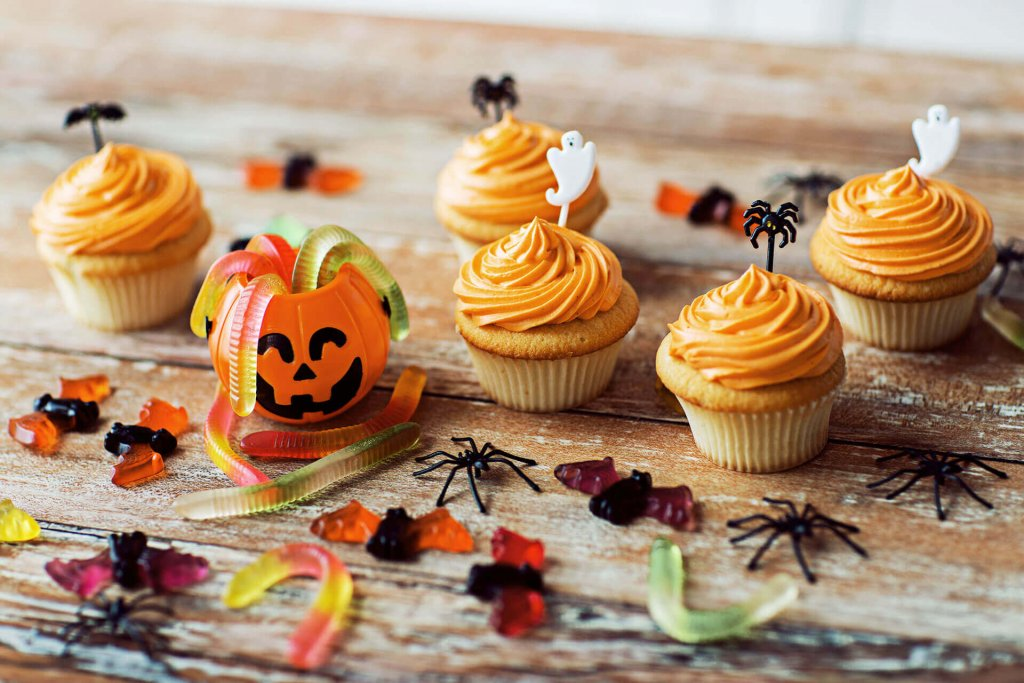 Halloween candy, cupcakes, and decorations on wooden table - halloween safety tips for dogs