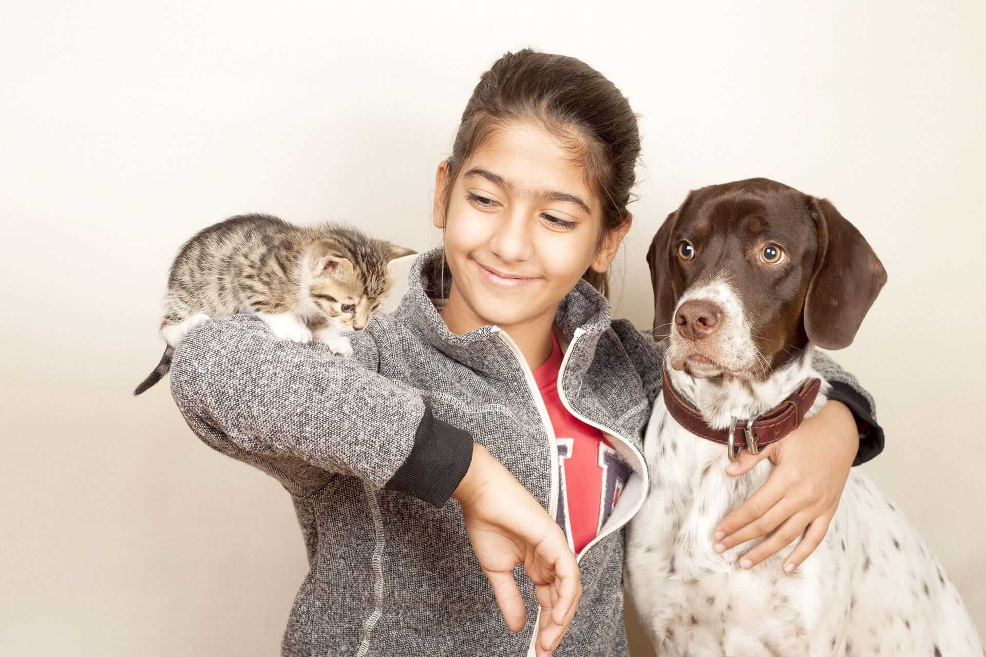 Cats and dogs with a young girl