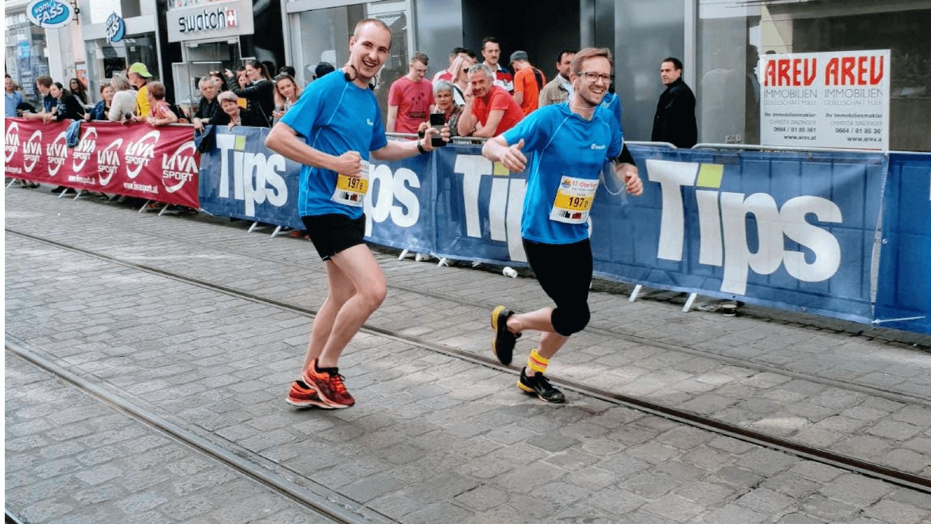 Teamsport beim Linz Marathon zwei Mitarbeiter laufen gemeinsam ins Ziel