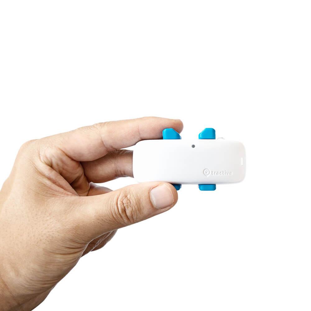 Photo d'une main tenant un GPS tractive blanc