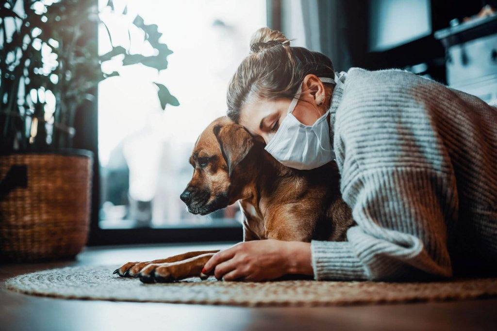Dog and woman with face mask - can dogs get coronavirus?