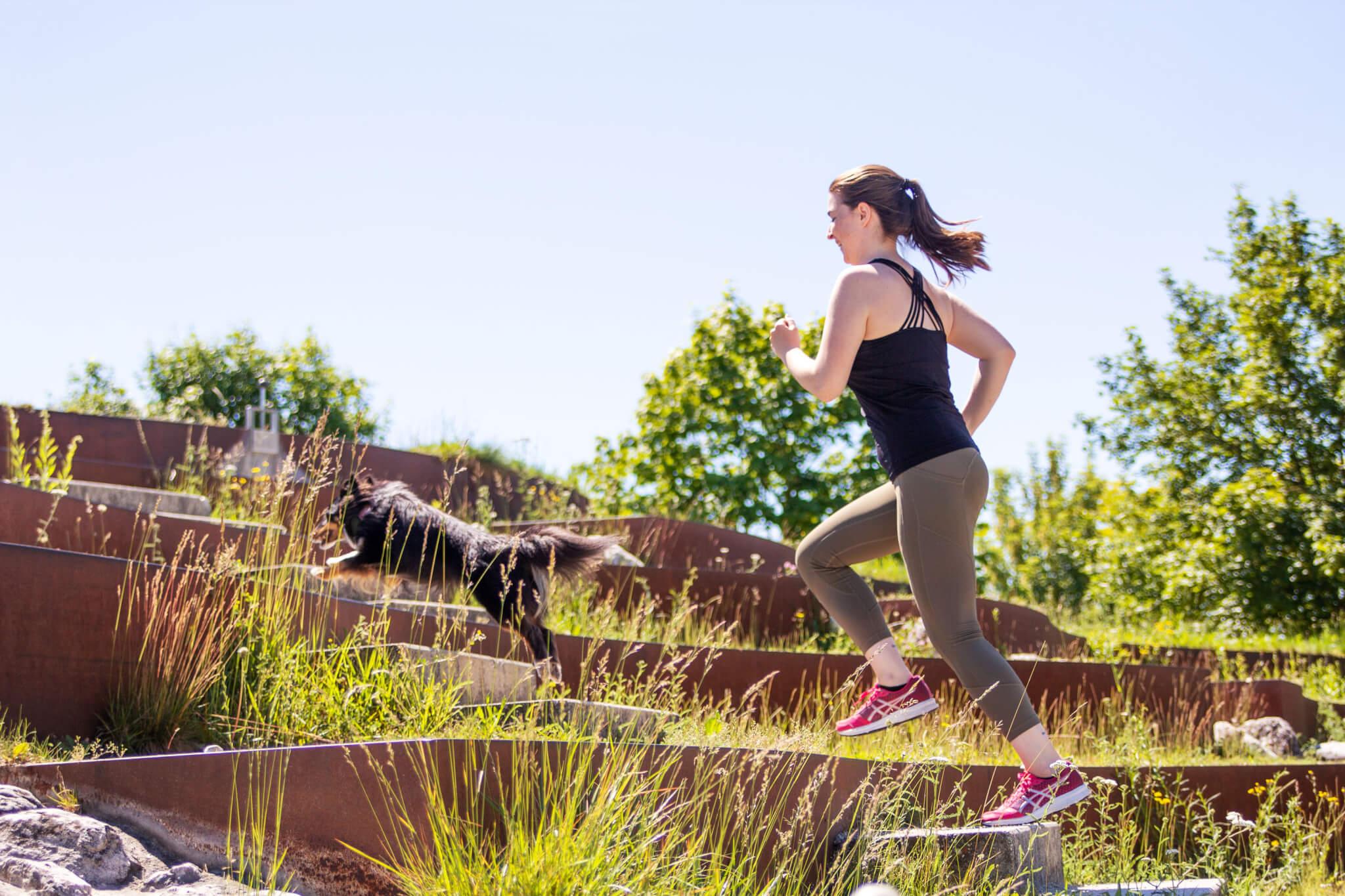 Frau läuft bergauf mit Hund