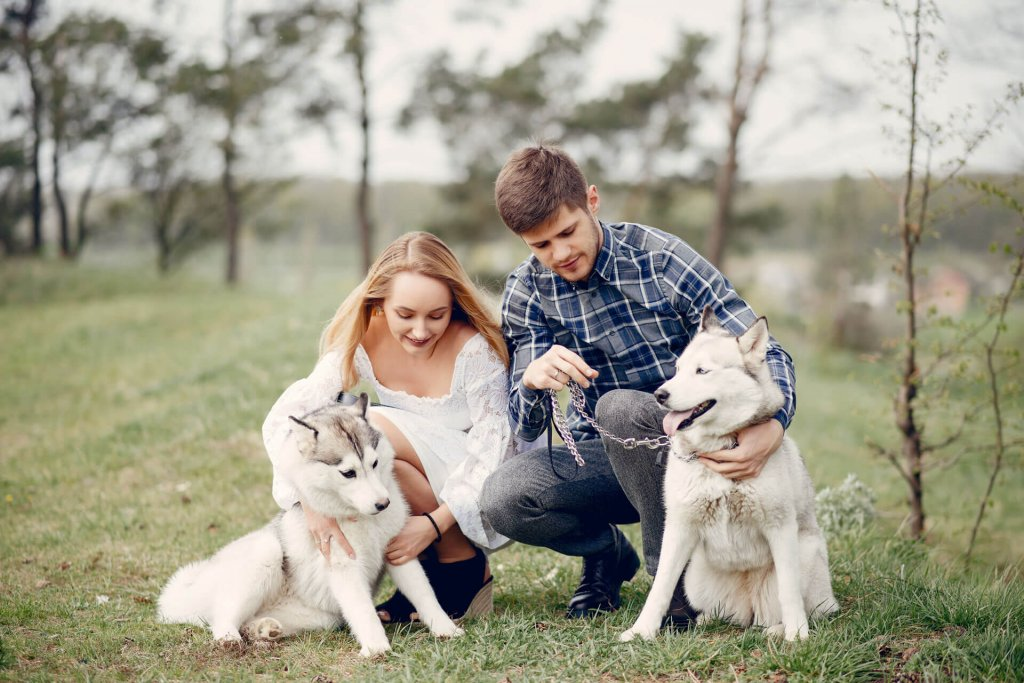 man and woman with dogs in nature - benefits of having a dog