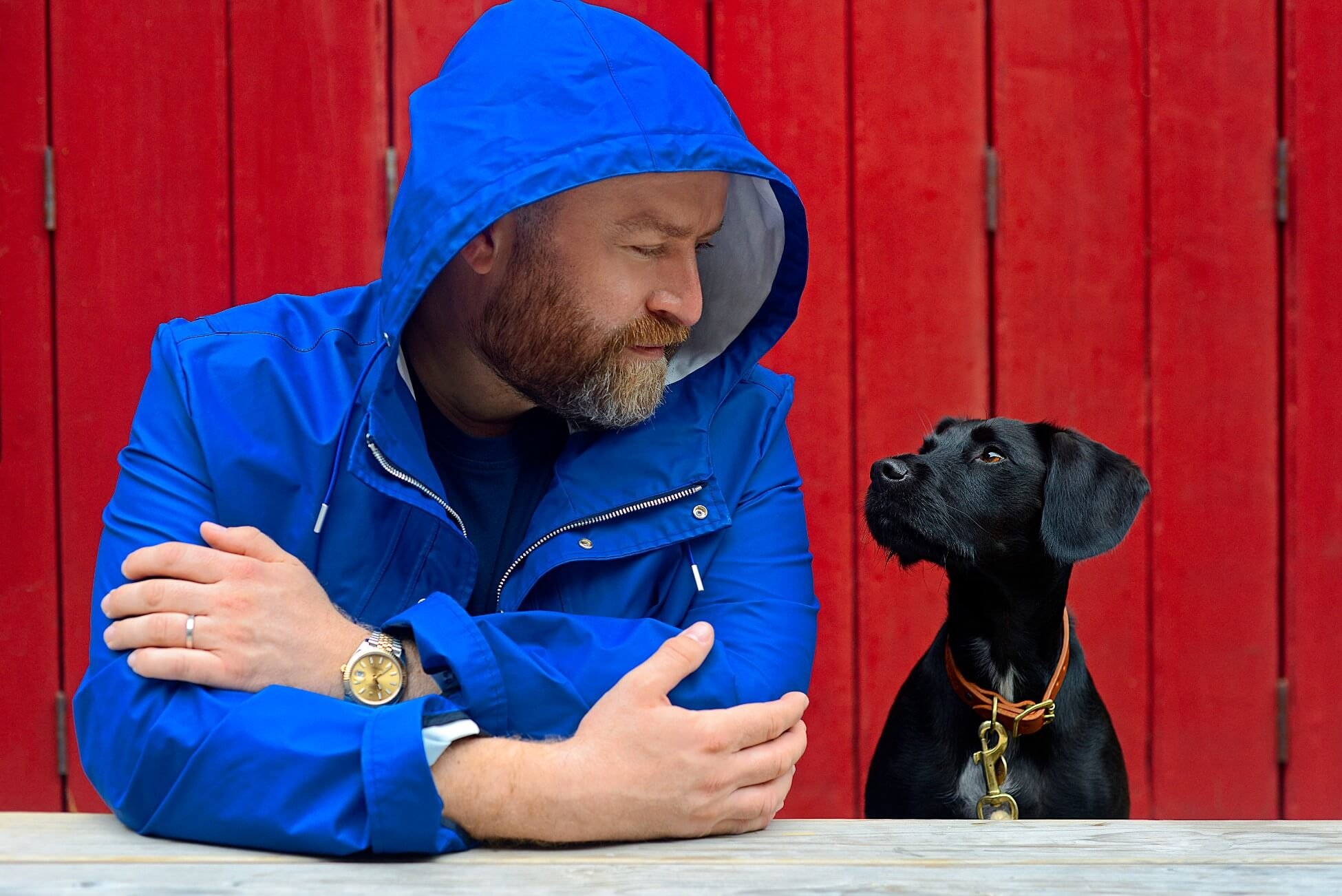 Oli Juste - man in blue coat and black dog with red background bonfire night