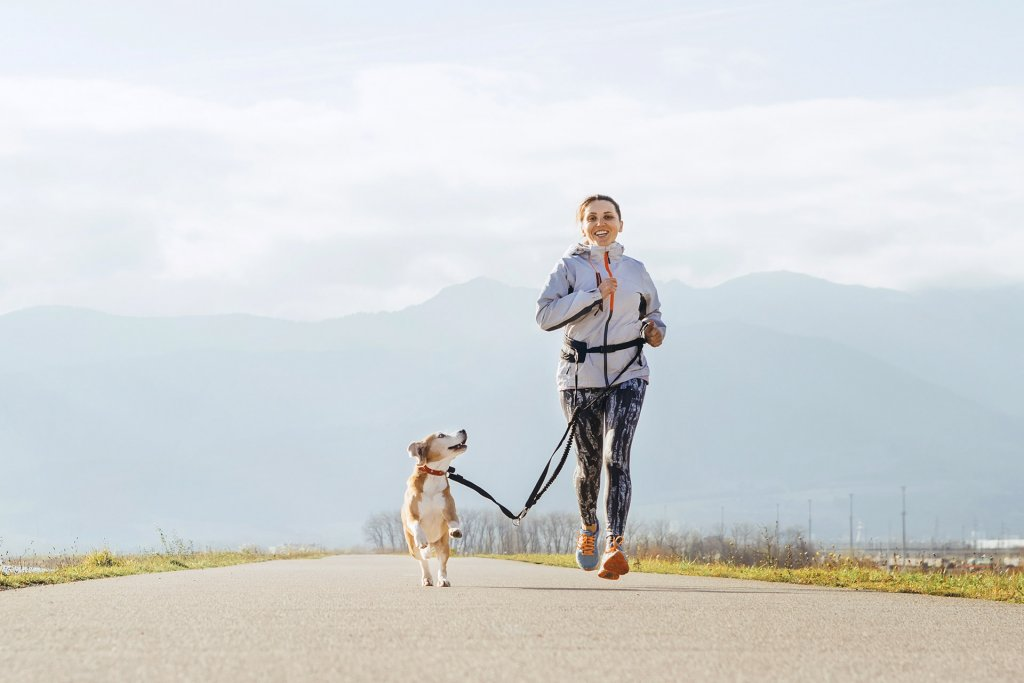 woman running with dog outside