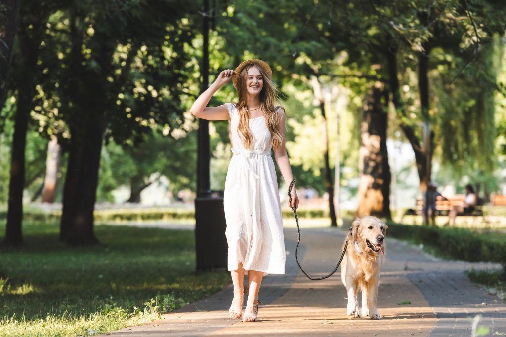 woman in white dress walking golden retriever dog on a leash outdoors, dog wearing Tractive GPS tracker