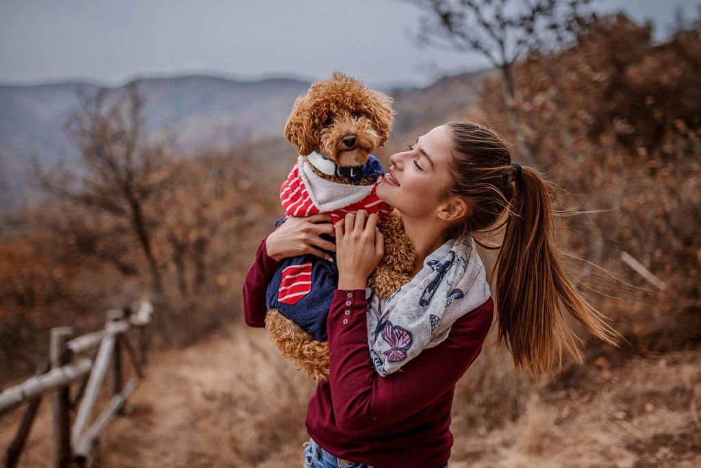 Frau hält Hund mit GPS Tracker in den Armen