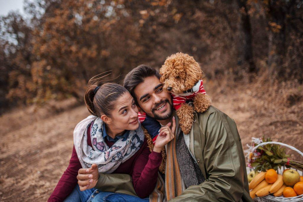 un homme, une femme et un chien en extérieur . Le chien porte un traceur GPS Tractive au cou