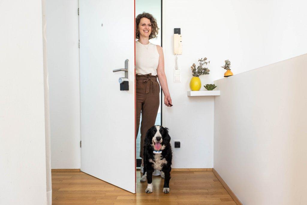 Frau mit Hund öffnet Tür mit Smart Lock