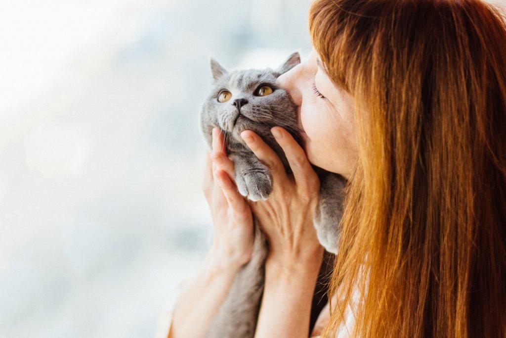 Frau mit roten Haaren knuddelt ihre graue Katze