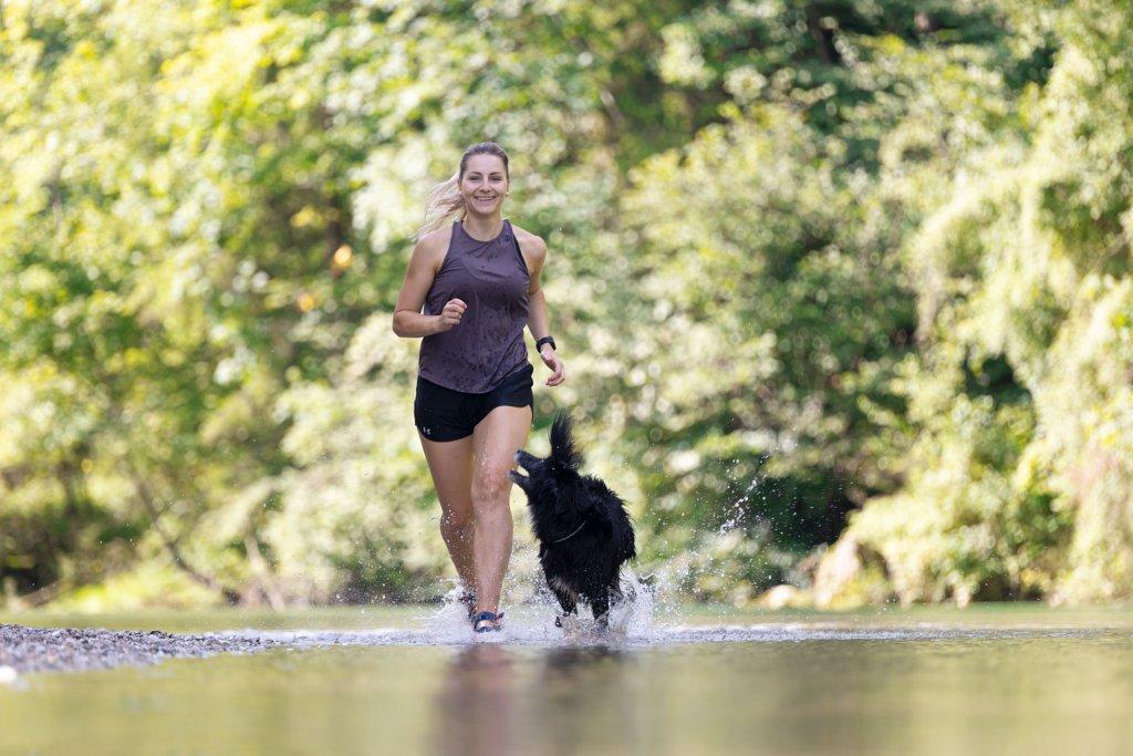 Mujer y perro corriendo en un río