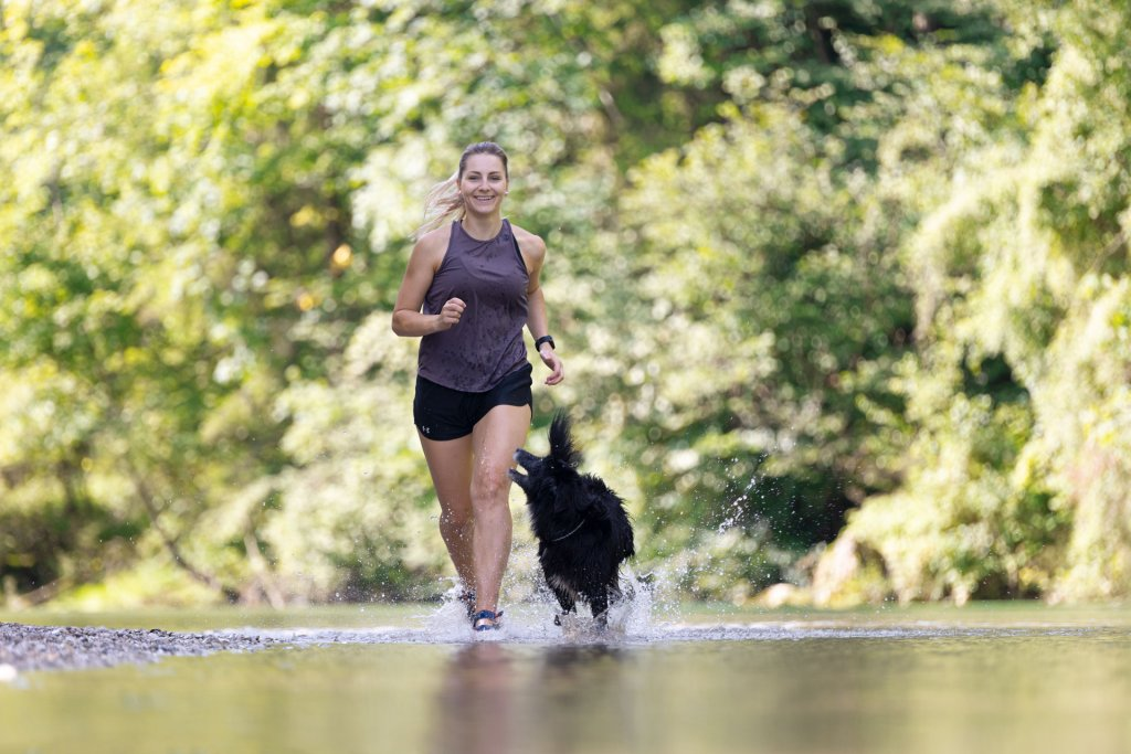 woman running outdoors with dog
