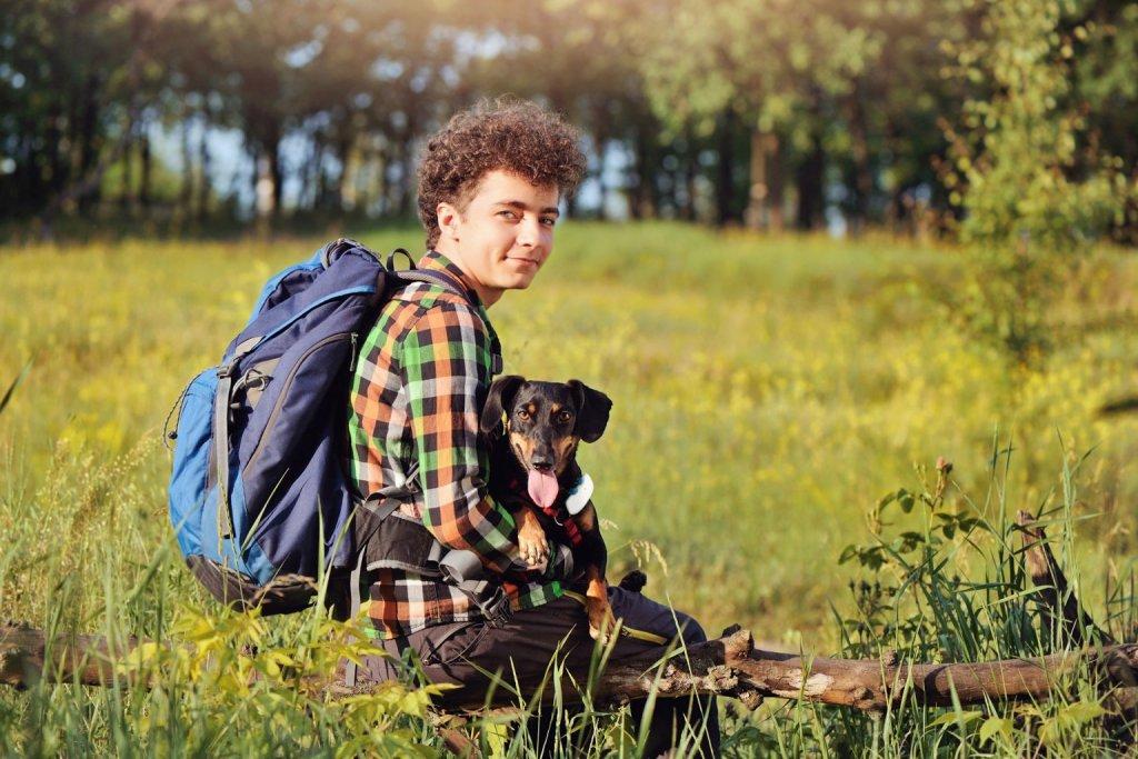 Hundebesitzer sitzt mit Rucksack und Hund auf dem Schoß in der Wiese auf einem Ast